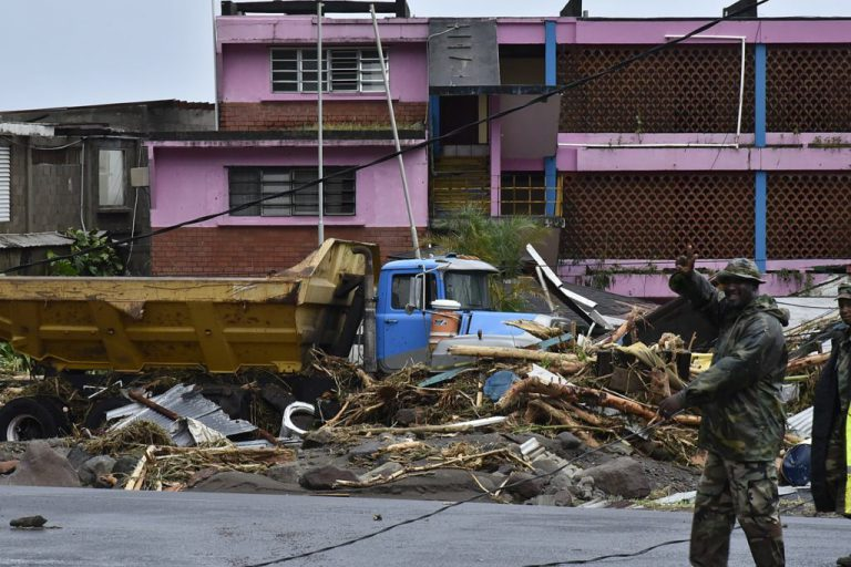 Truck picking up wind damaged building materials